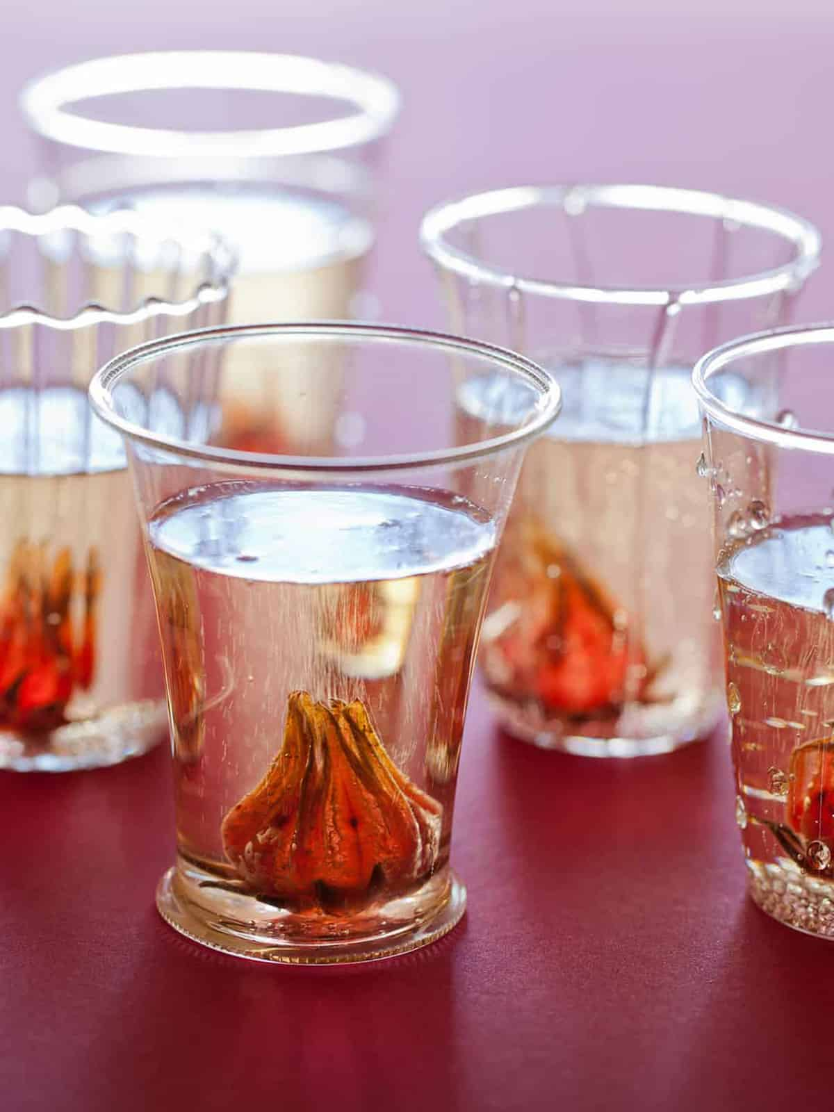 A close up of glasses of hibiscus ginger champagne cocktails.