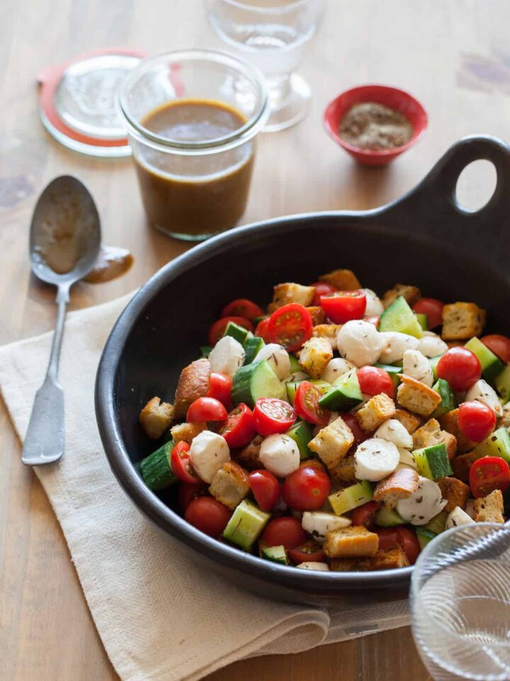 Panzanella salad in a serving bowl with a jar of dressing and a spoon.