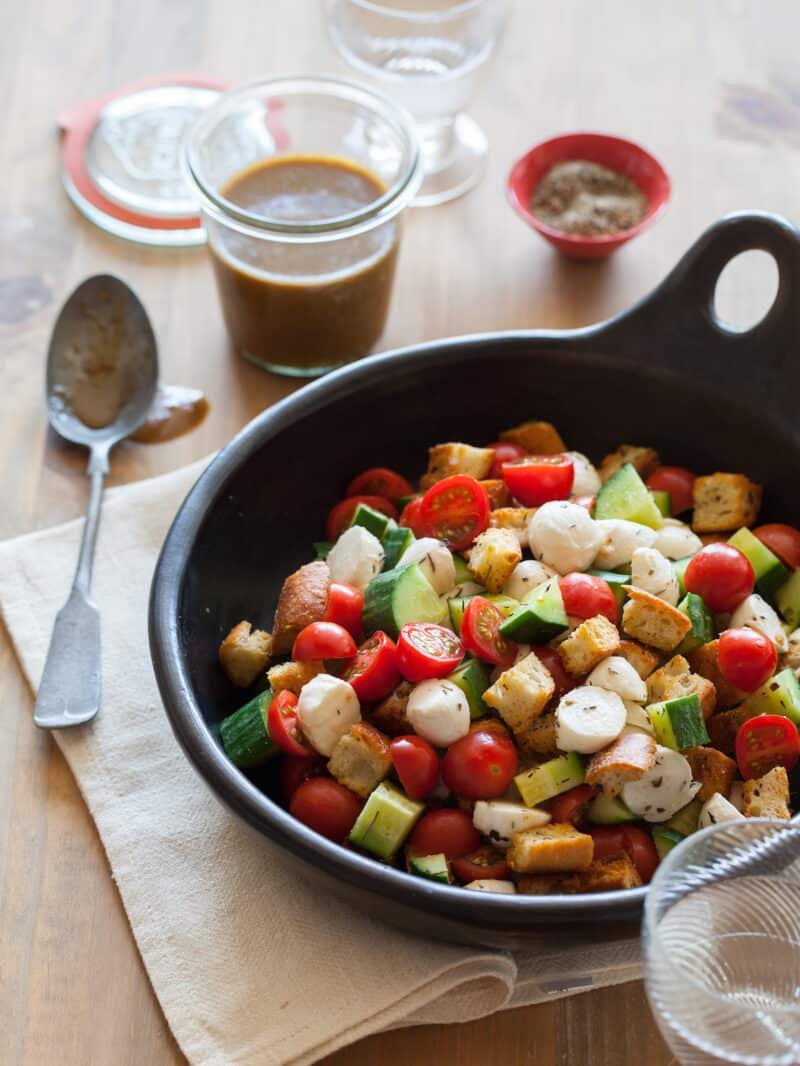A bowl of panzanella salad with a jar of dressing and a spoon on the side.