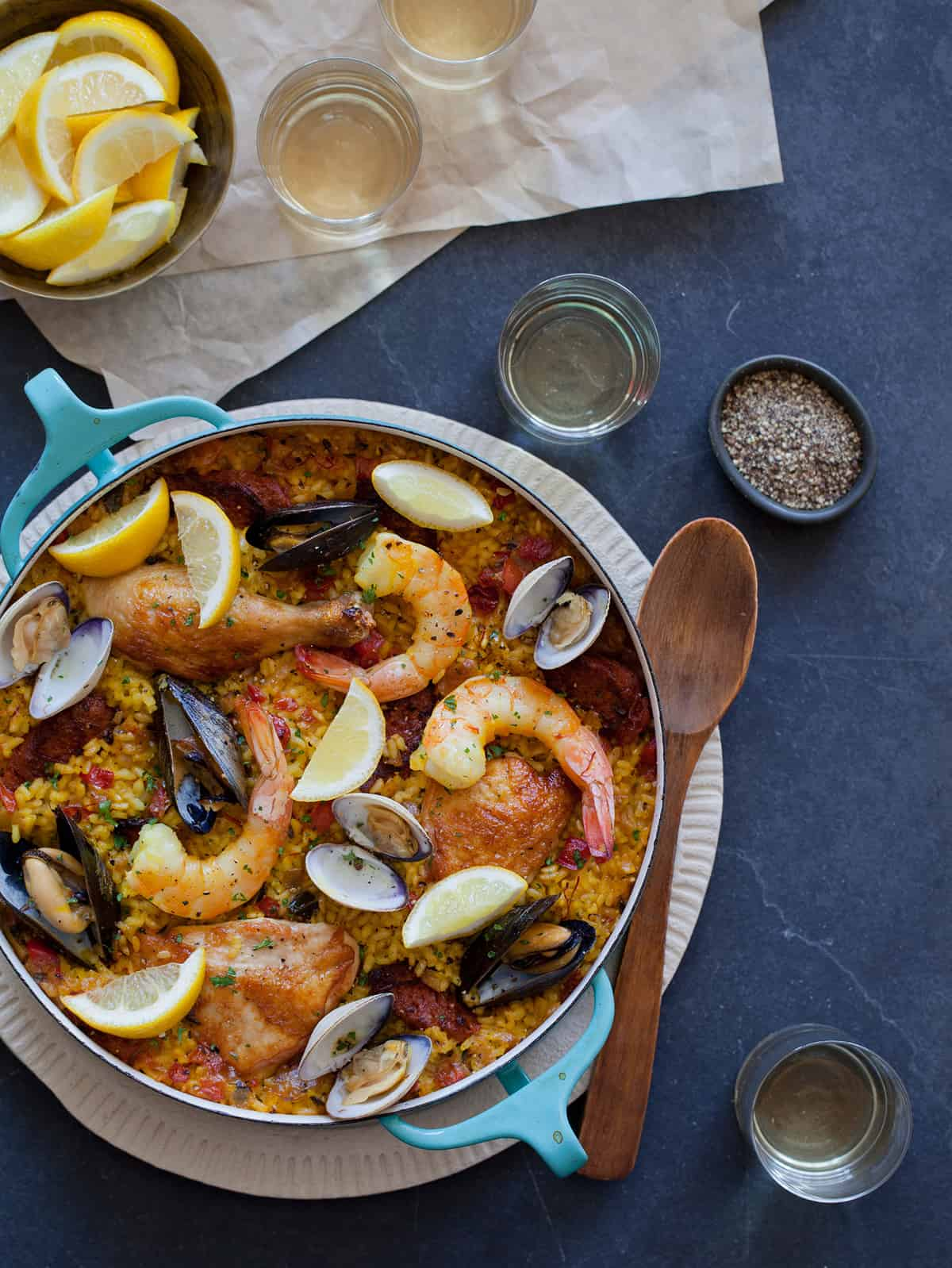 A pot of paella with spices in bowls, lemon wedges, and a wooden spoon.