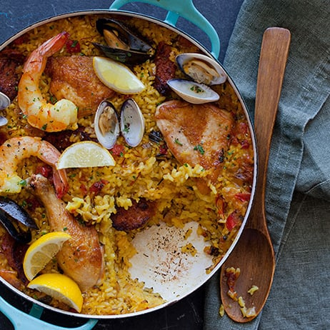 Paella in a pot pot with a scoop taken out and a wooden spoon next to it.
