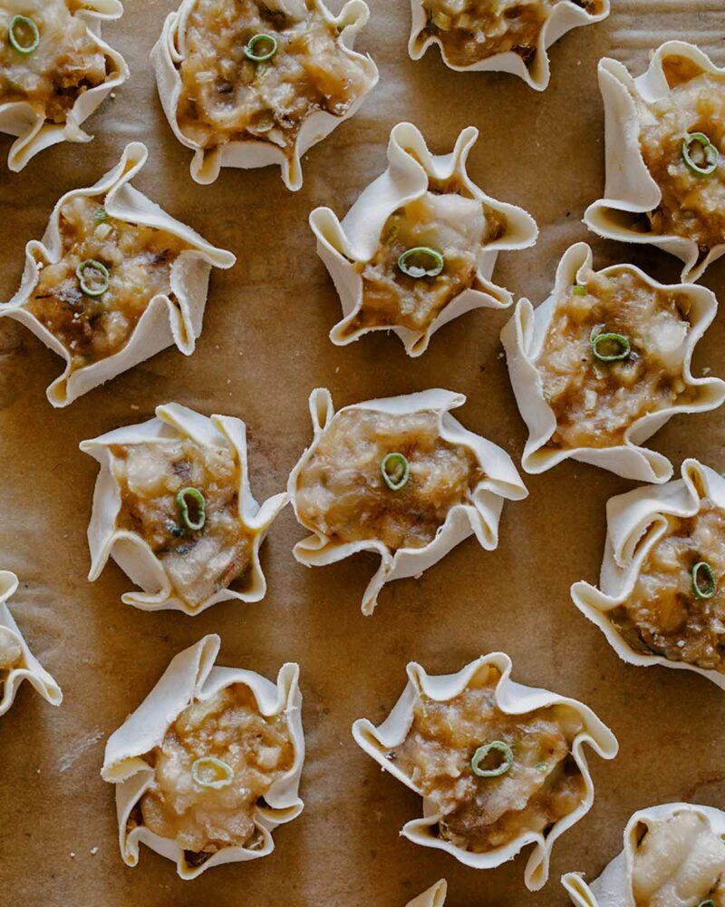 Overhead of 14 frozen shrimp shumai on parchment paper as per directions.