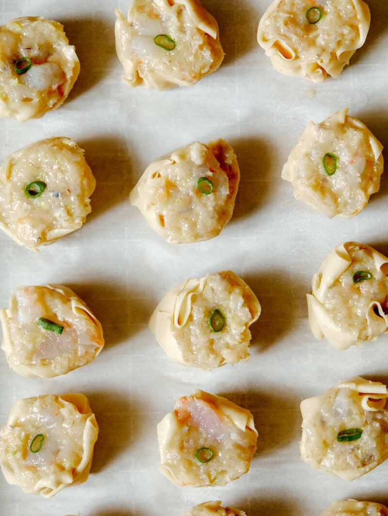 overhead of 12 raw shrimp shumai on parchment paper
