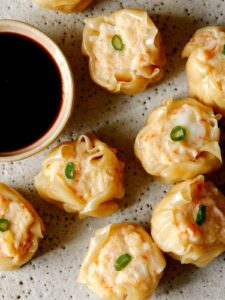 A close up of shrimp shumai with sauce on the side.