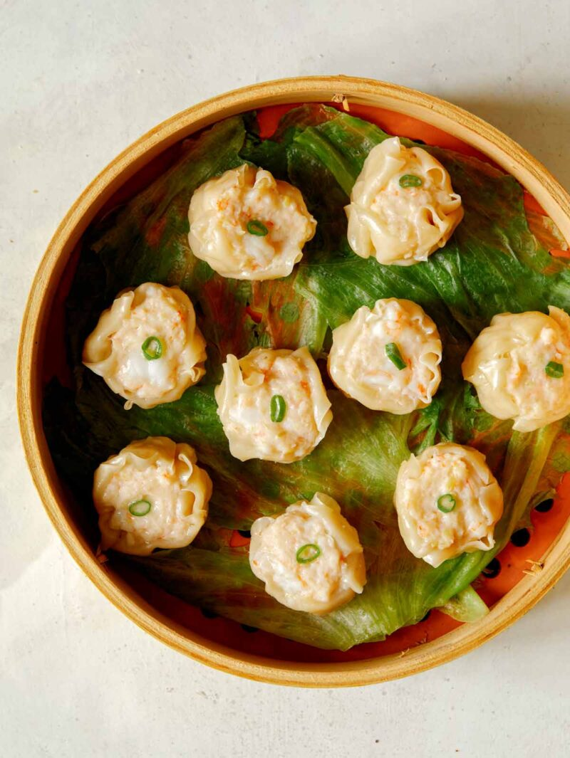 overhead of 9 Freshly steamed shrimp shumai in steamer basket