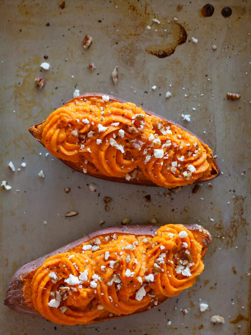 A close up of twice baked sweet potatoes with chopped pecans and feta.