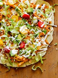 A close up of an arepa pizza with chipotle chicken and cilantro yogurt sauce.