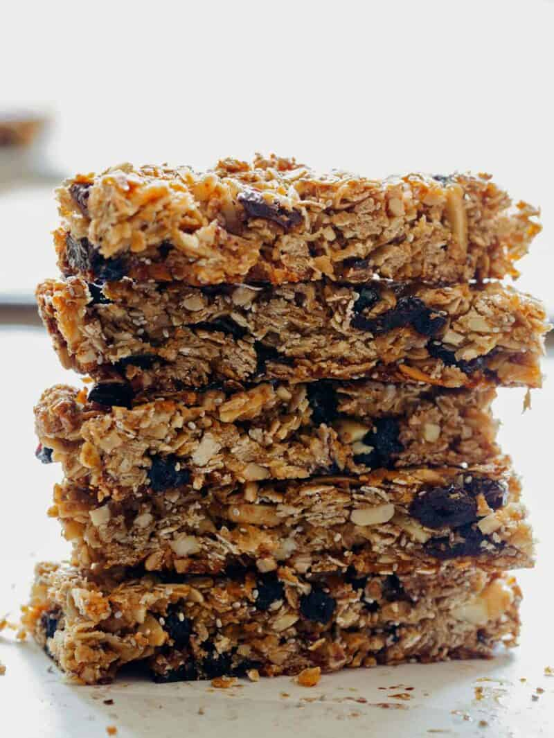A close up of stacked homemade granola bars with coconut and dried cherries and blueberries.
