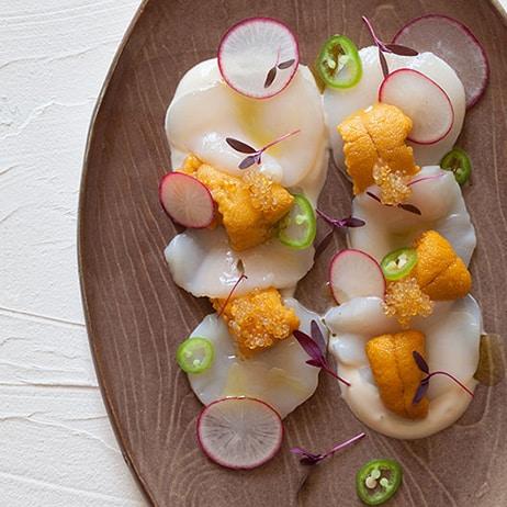 Scallop and uni crudo on a platter.