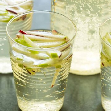 A close up of glasses of sparkling apple sangria.