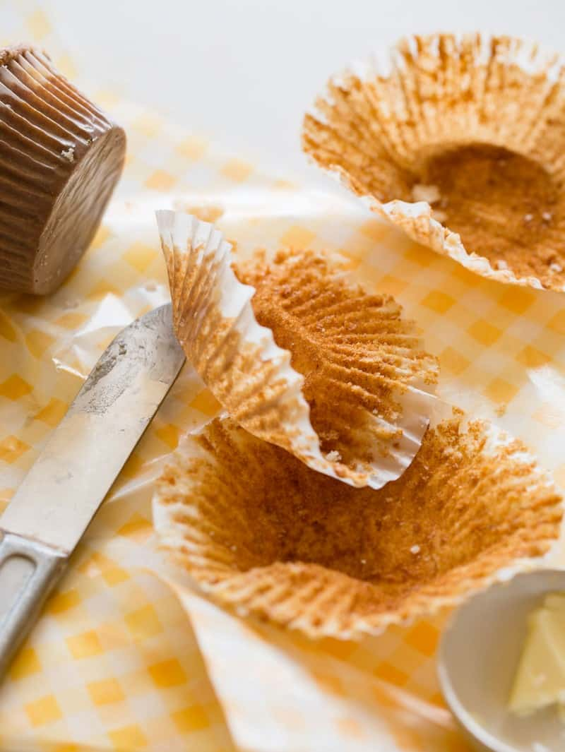 A close up of empty muffin liners with a butter knife.