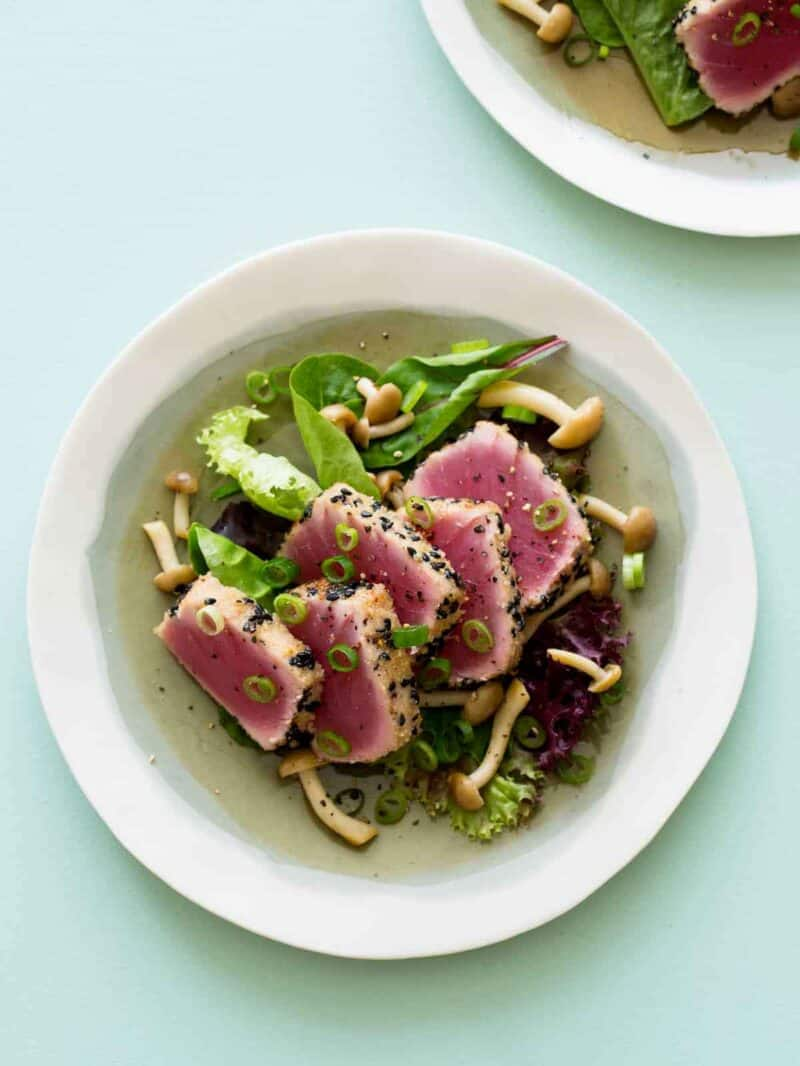 A bowl of black sesame and almond crusted ahi tuna on mixed greens with beech mushrooms.