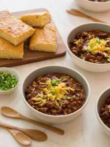 Several bowls of kitchen sink chili topped with cheese and green onion with cornbread.