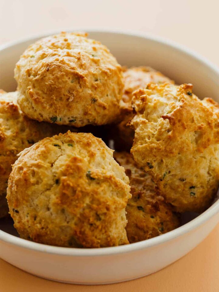 Close up of a bowl of sour cream and chive drop biscuits.