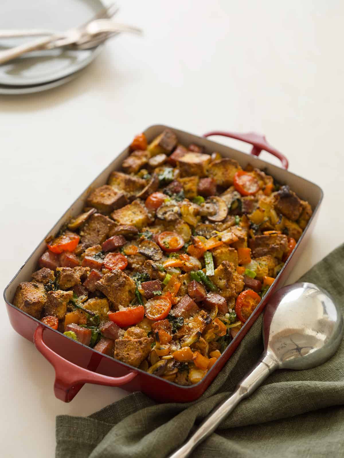 A baking pan of savory bread pudding with a large serving spoon.