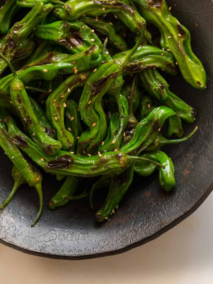 A close up of blistered shishito peppers in a dark bowl.