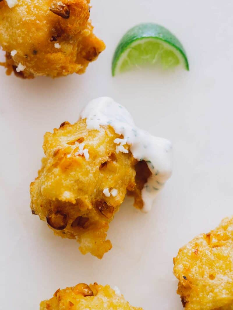 A close up of elote fritters dipped in cilantro mayo with lime wedges.