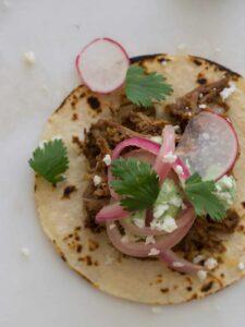 A close up of a cochinita pibil taco.