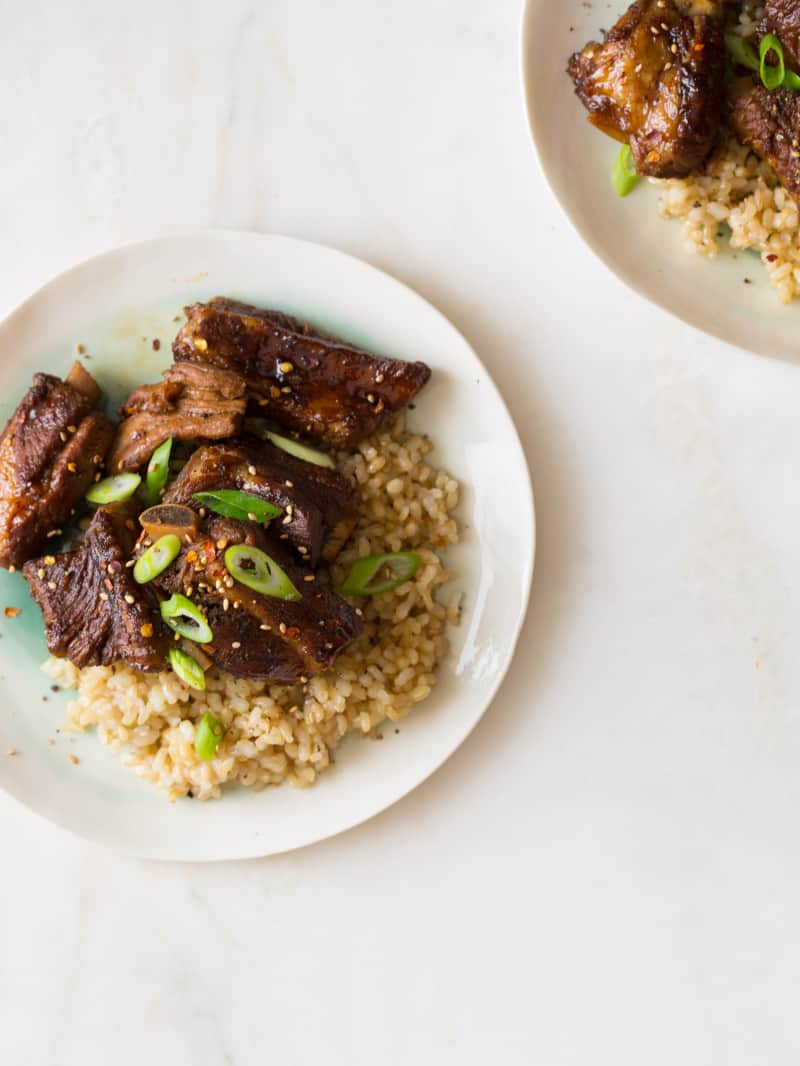 Plates of honey soy braised ribs over brown rice with thinly sliced green onions.