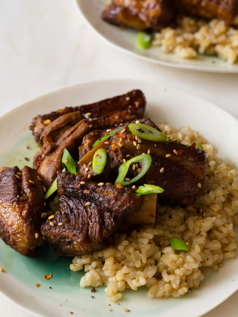 A close up of honey soy braised ribs over brown rice with thinly sliced green onions.