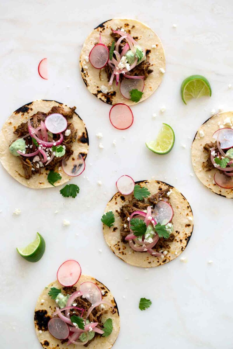 Several cochinita pibil tacos with radishes and lime wedges.