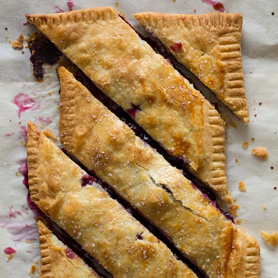 Blueberry slab pie cut horizontally on a piece of parchment paper.