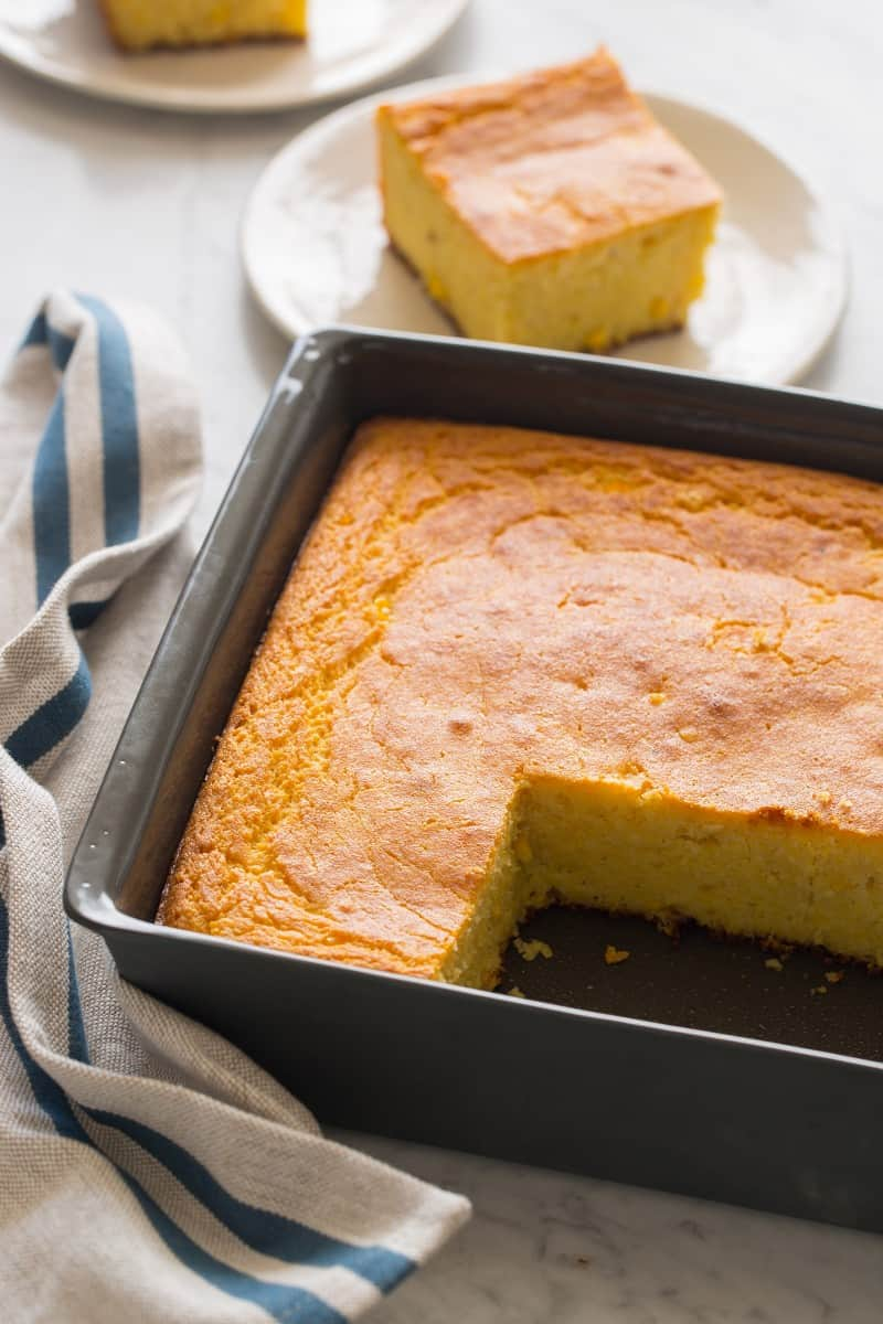 A pan of buttermilk cornbread with pieces cut out and plated.