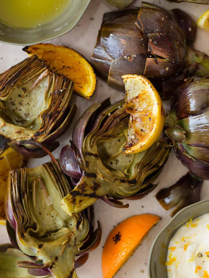 Grilled Artichokes on a platter with melted butter and aioli.