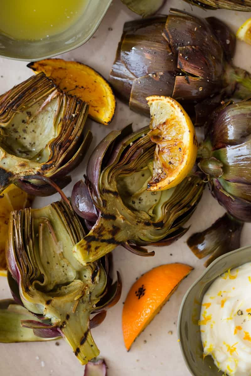 A close up of grilled artichokes with orange and lemon wedges and aloe on the side.