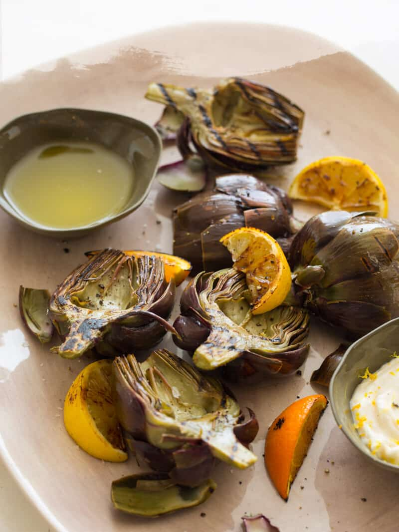 A close up of grilled artichokes with clarified butter and roasted garlic aoli.