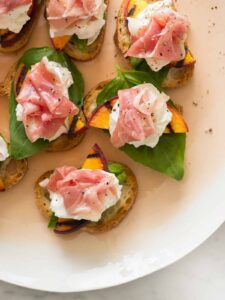 Grilled peach and burrata crostini on a platter.