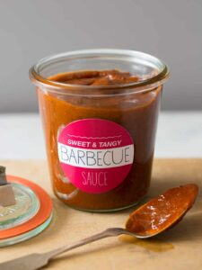 A labeled glass jar of sweet and tangy BBQ sauce, the lid, and a coated spoon.