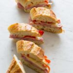 Several bocadillo bites of ham, cheese, and pickled cherry peppers on a baguette.
