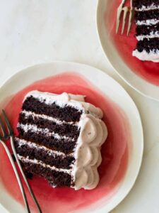 Slices of devils food cake with real strawberry frosting on plates with forks.