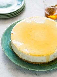 A goat cheese and yogurt cheesecake drizzled with honey with extra plates.