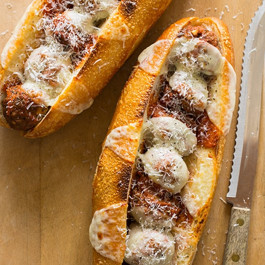 Two meatball sandwiches on a cutting board with a knife next to it.