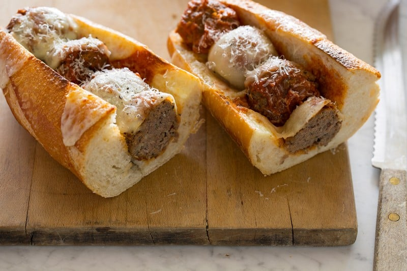 A meatball sub cut in half to see the meatballs on a cutting board.