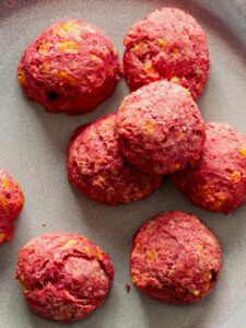 A close up of several beet and cheese biscuits.