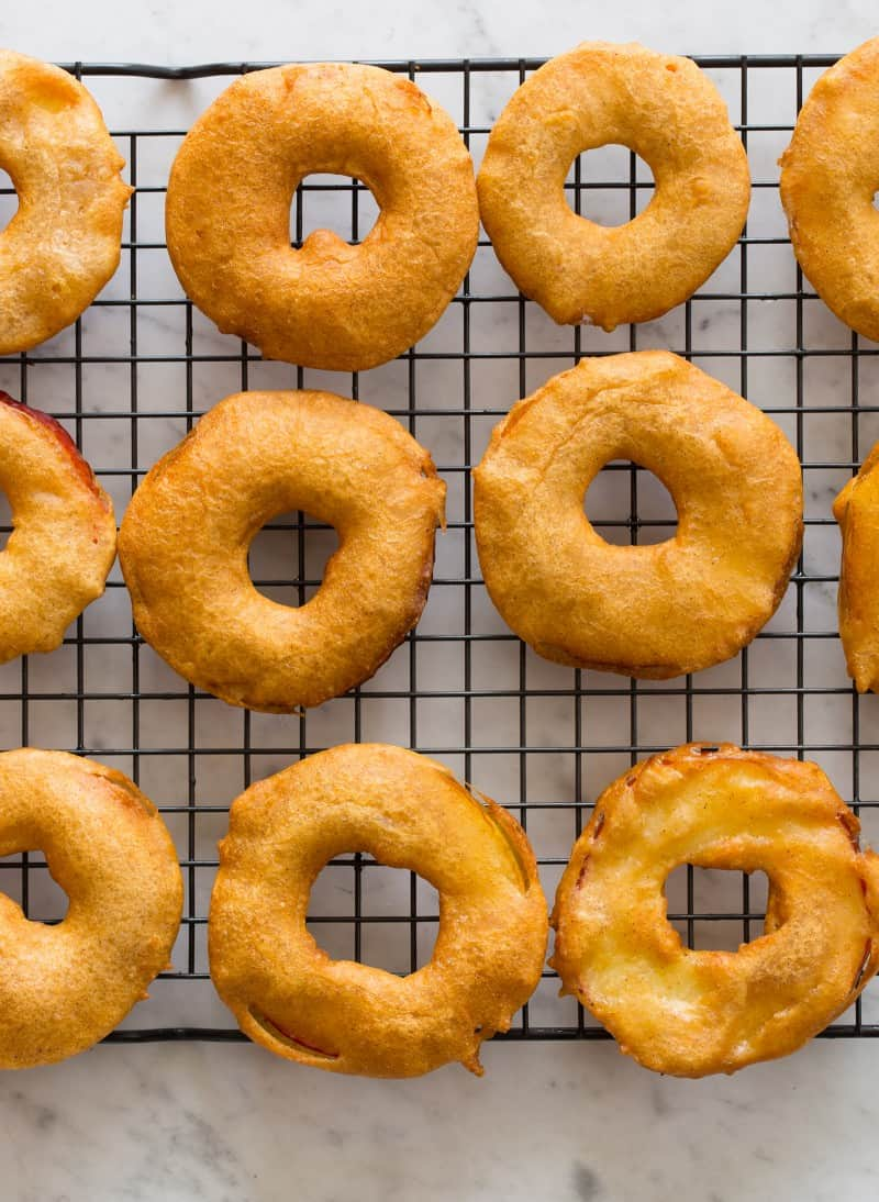 Apple fritter rings on a wire rack.