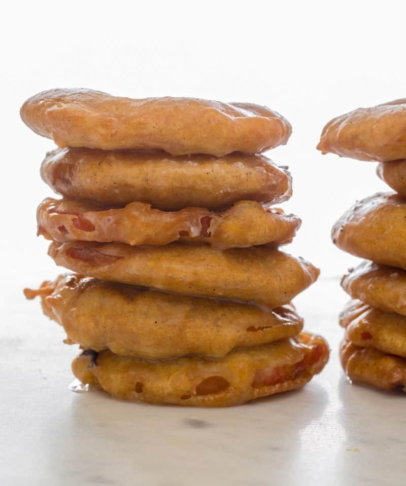 Apple pie fritter rings stacked on a surface.