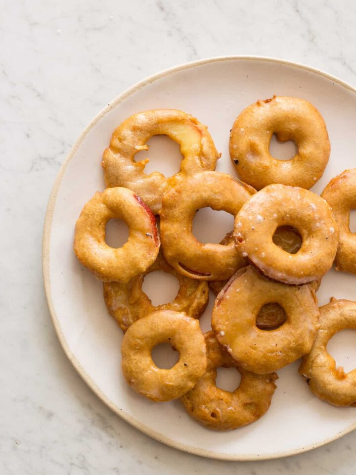 A plate of stacked apple fritter rings with vanilla bean glaze.
