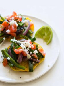 A close up of a plate cachapas topped with veggies and a lime wedge.