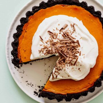 A whole pumpkin pie with chocolate crust and whipped cream with a slice taken out.