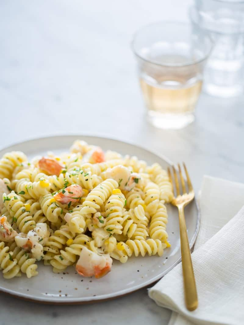 Lobster and corn pasta on a plate with a glass of wine in the background.