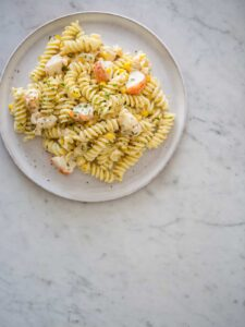 Lobster and corn pasta with white wine and tarragon cream sauce on a plate.