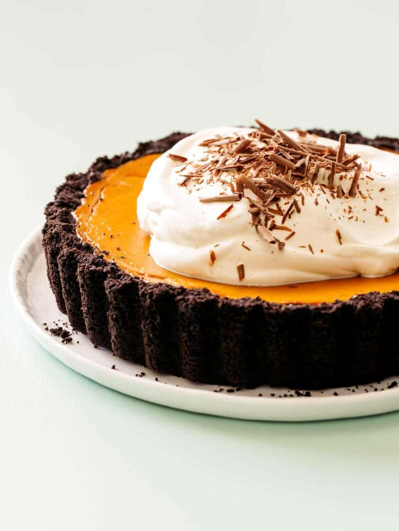 A close up of a whole pumpkin pie with chocolate crust, whipped cream, and chocolate shavings.