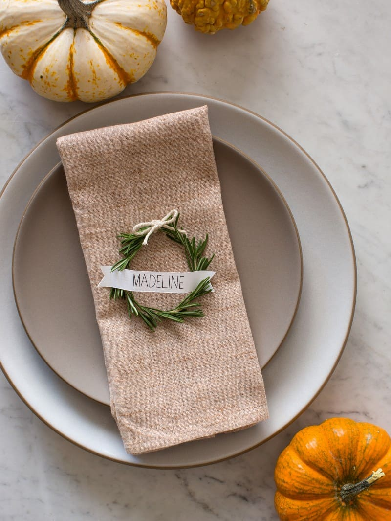 A place setting with neutral linens, a rosemary wreath place card, and small pumpkins.