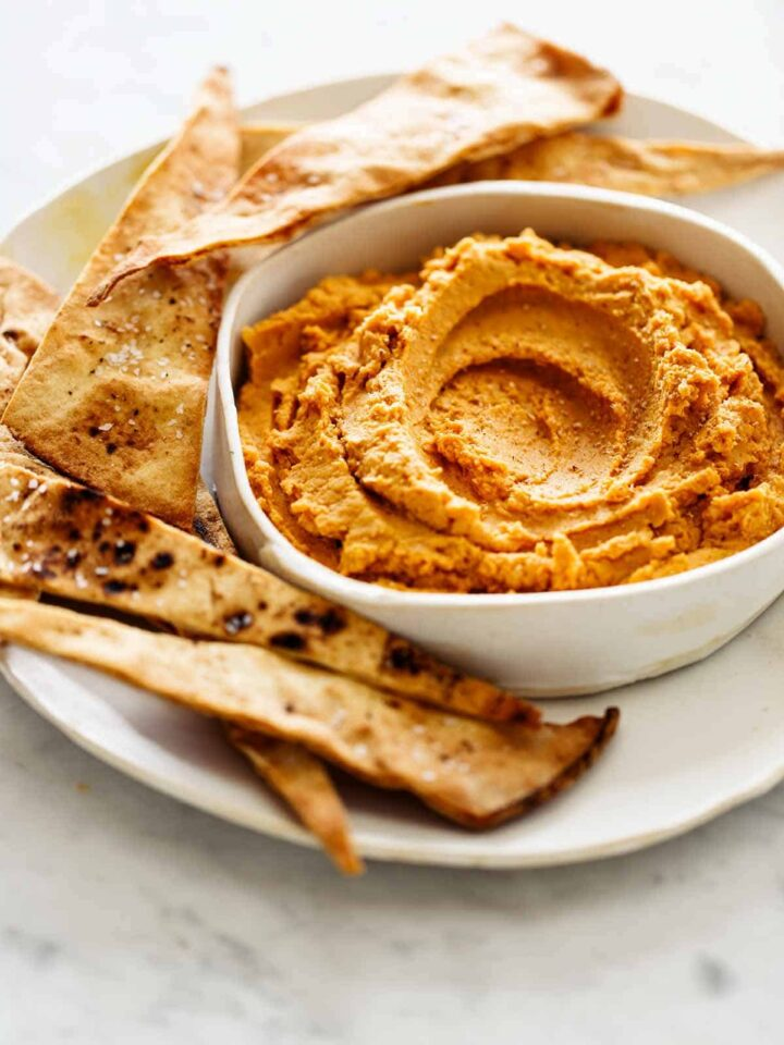 A close up of savory pumpkin hummus on a plate with baked pita chips.