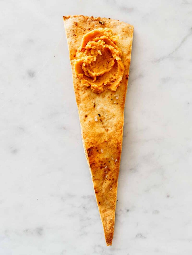 A dollop of pumpkin hummus on a seasoned pita chip