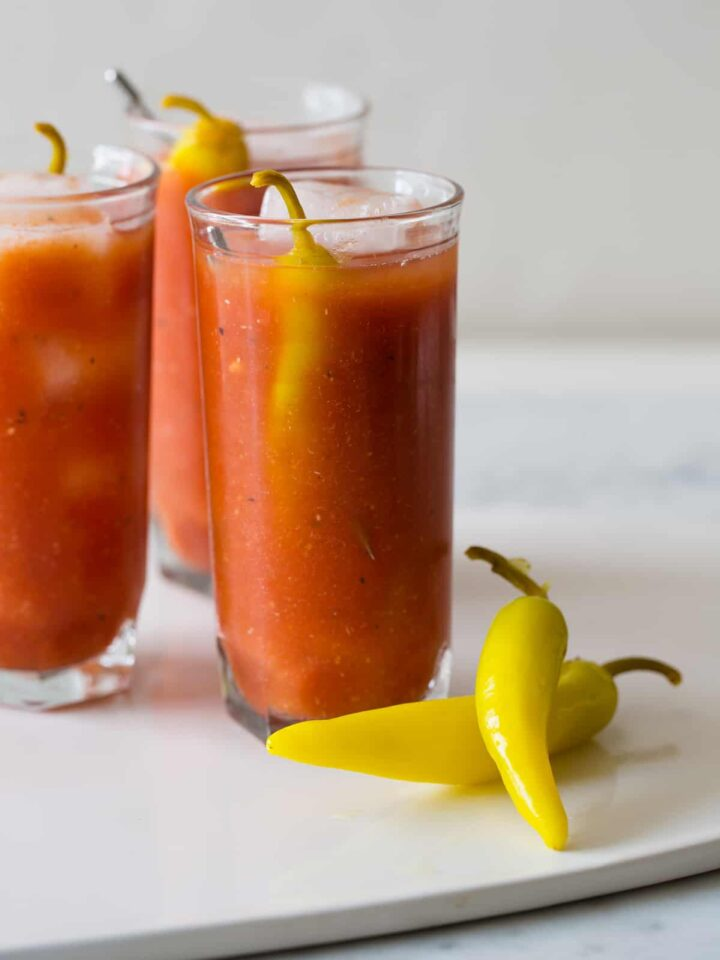 Several simple bloody marys garnished with pickled peppers.